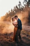 Beautiful Engagement Photography: Engaged couple standing together with coloured smoke haze behind them