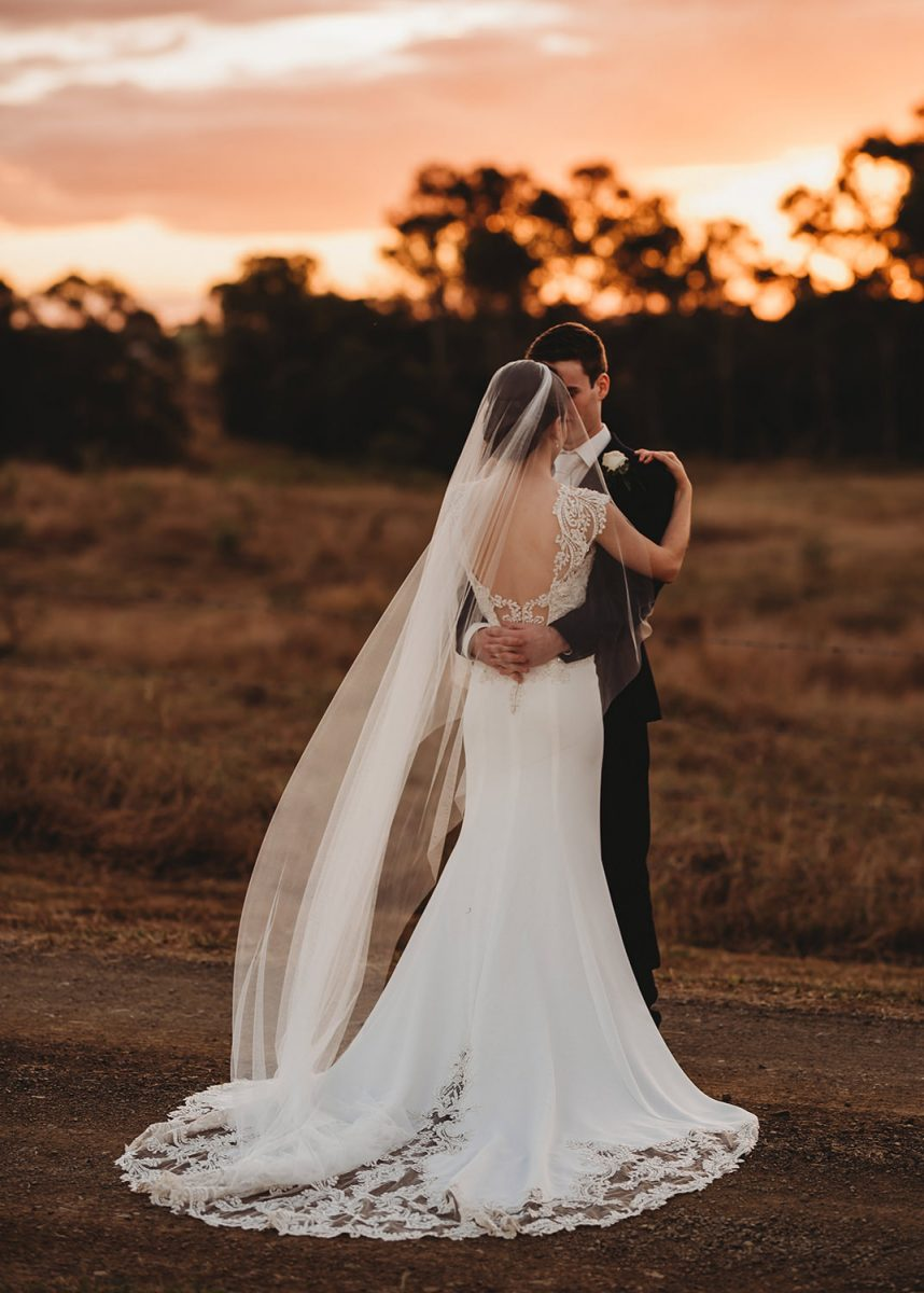 Sunset Wedding Photography: Couple standing together during sunset. Bride wears a cathedral length veil.