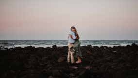 couple standing on rocks at the beach