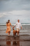 couple with labradoodle at the beach