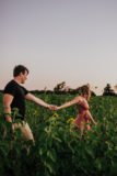 couple walking through sunflower field