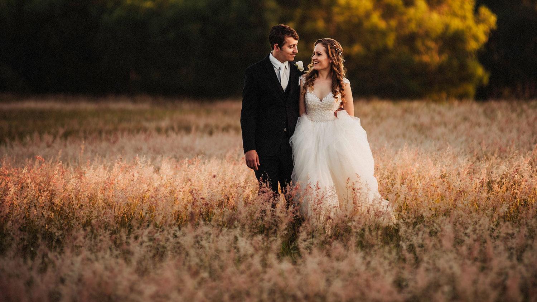 Bride Groom walking in a field