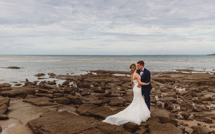 Bride and Groom standing on rocks at the Beach