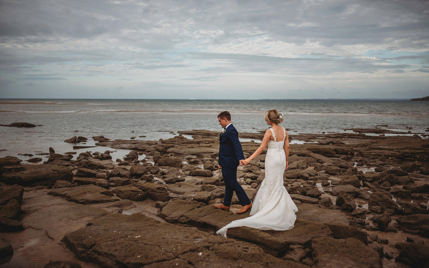 groom and bride walking on the rocks at the beach