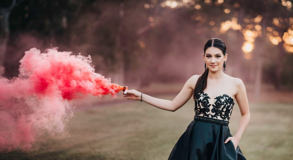 Prom girl wearing black strapless gown and holding a pink smoke boom.
