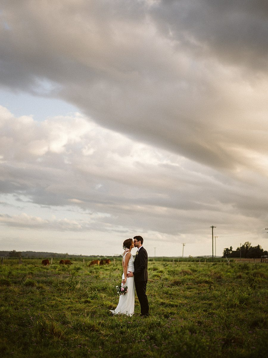 Couple Kissing in a field at sunset