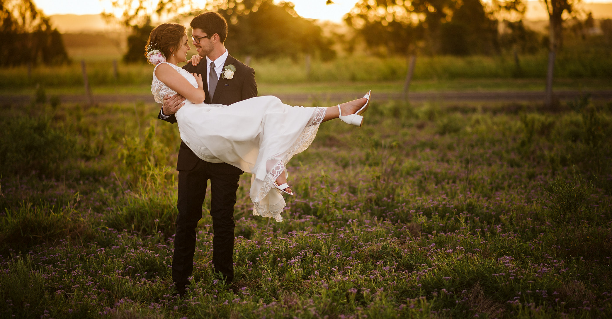 Groom carrying Bride at Sunset