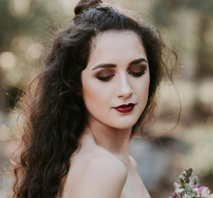 Styled Model wearing strapless vintage gown. Long dark curly hair and holding a bouquet.