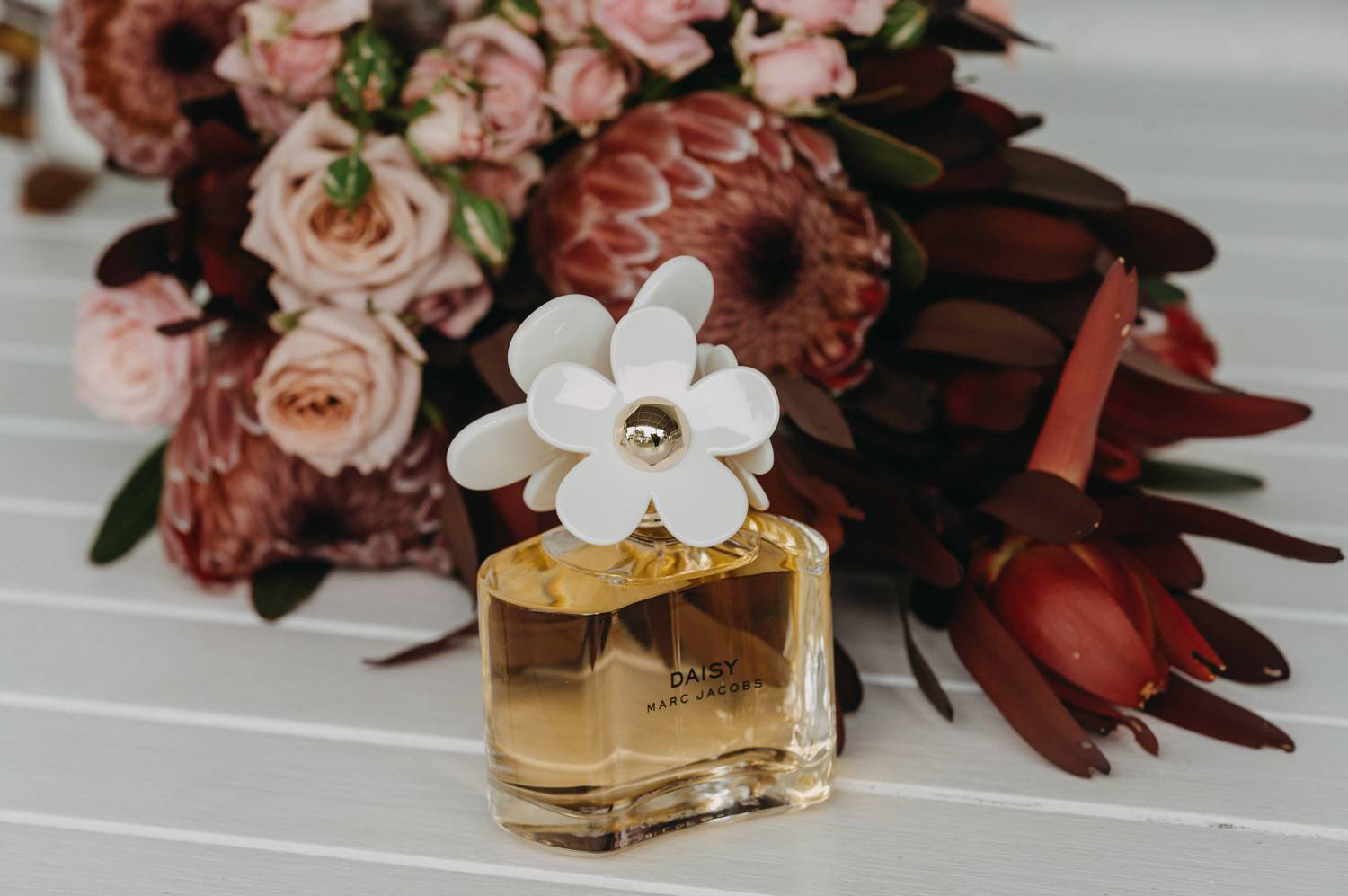 Perfume bottle in front of flowers