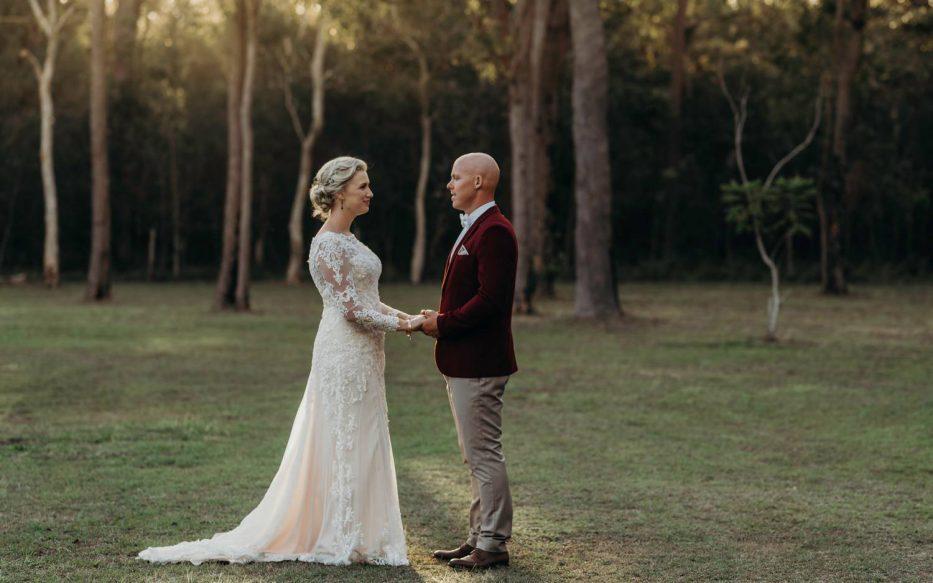 Bride and Groom holding hands in open field