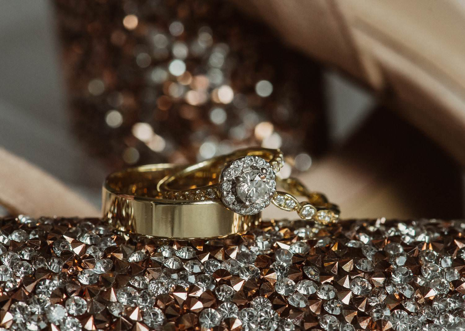 Wedding and Engagement rings on glittery surface.