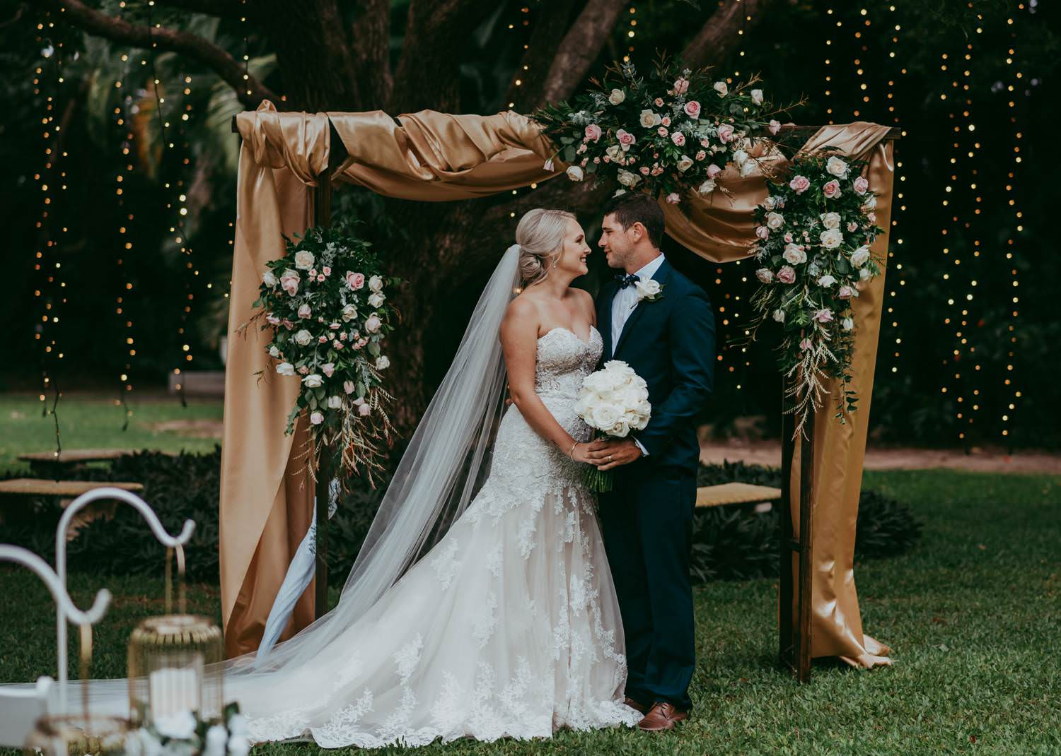 Bride and Groom standing in front of a arch with flower garlands and gold fabric