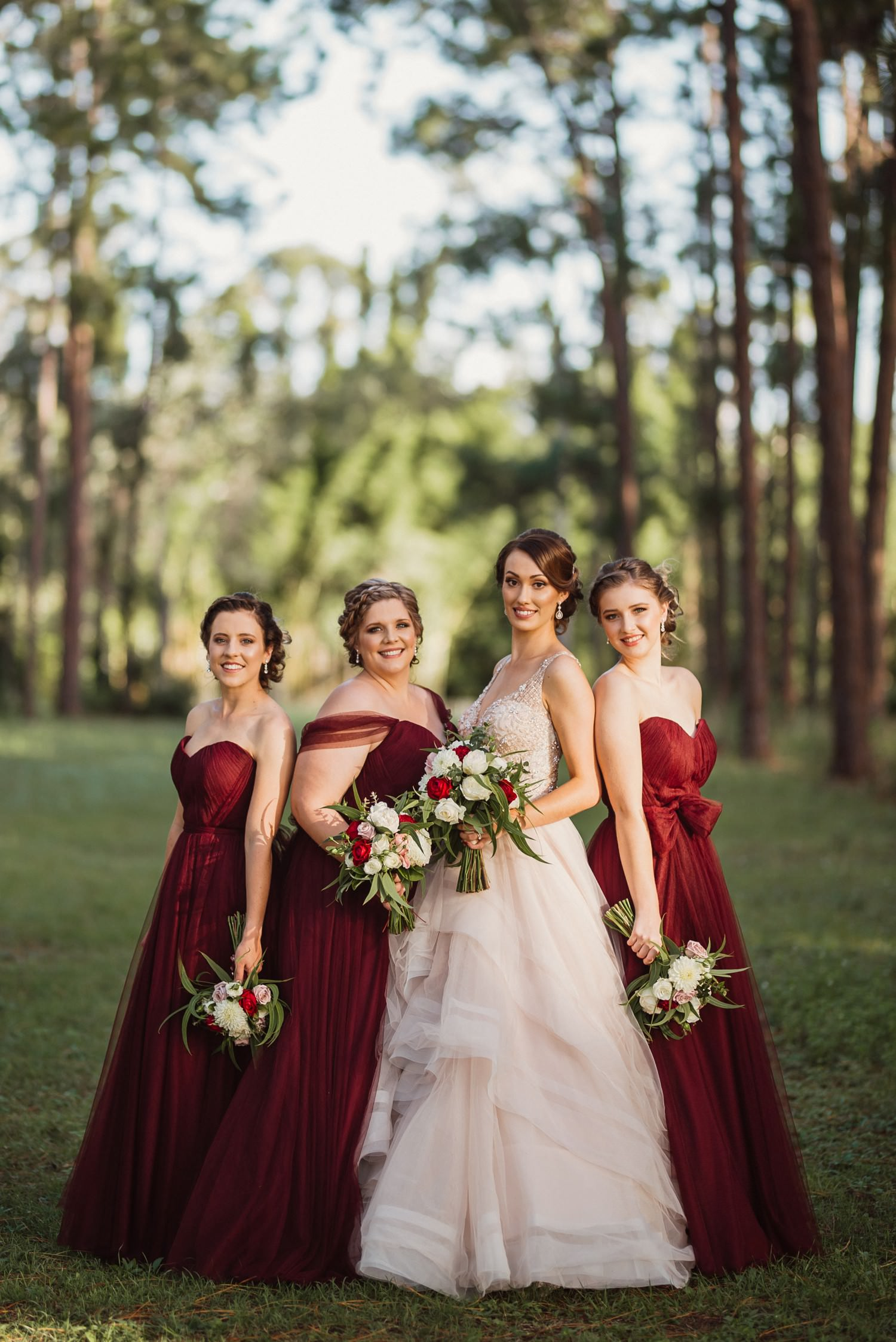 Bride with bridesmaids wearing merlot coloured dresses