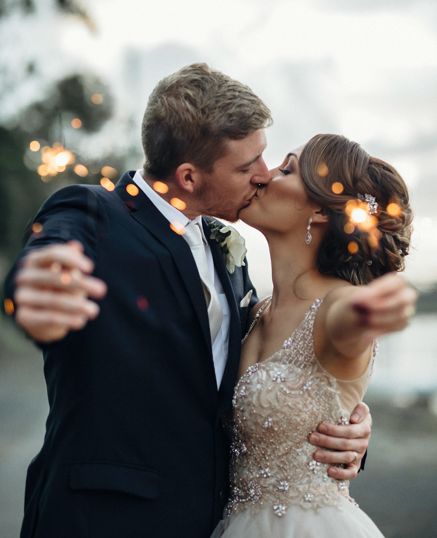 Couple kissing while holding sparklers