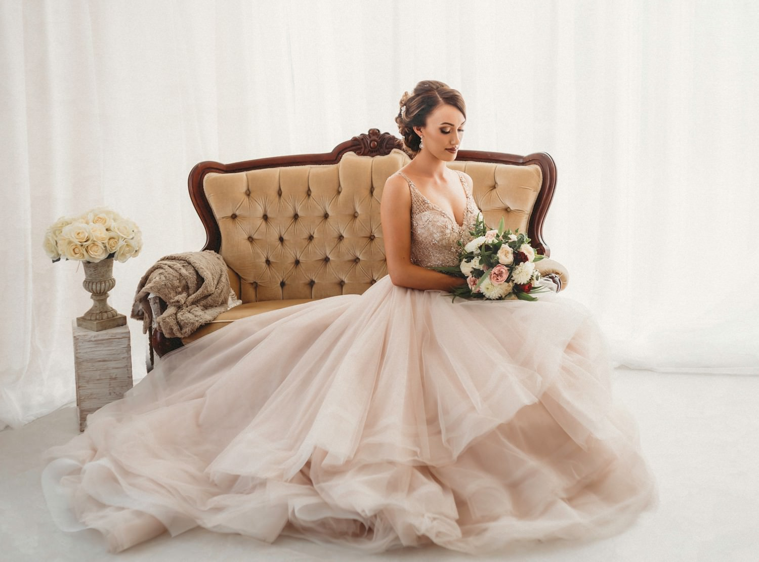 Bride in wedding gown sitting on velvet chair