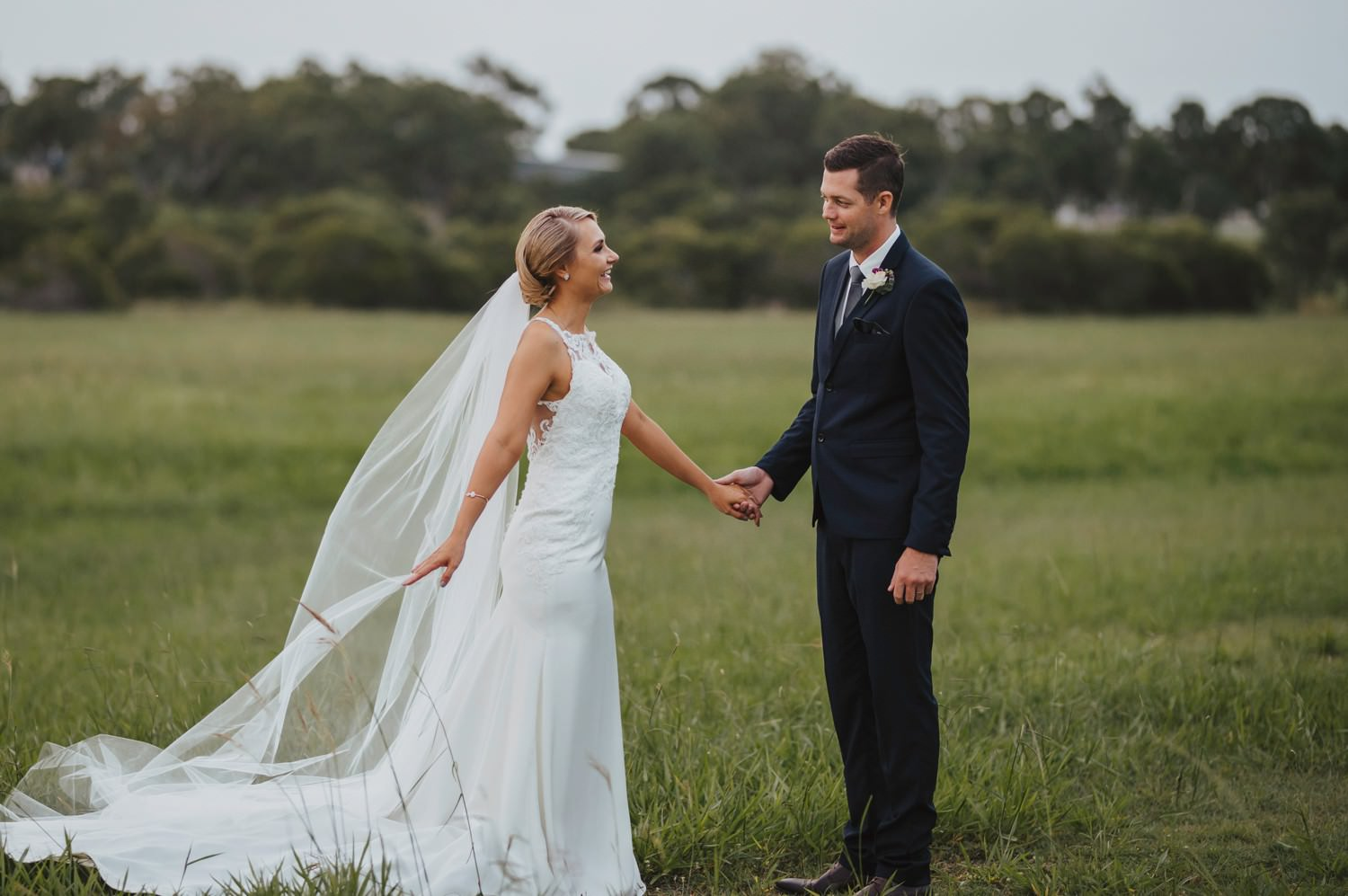 Bundaberg Bride and Groom holding hands in an open field