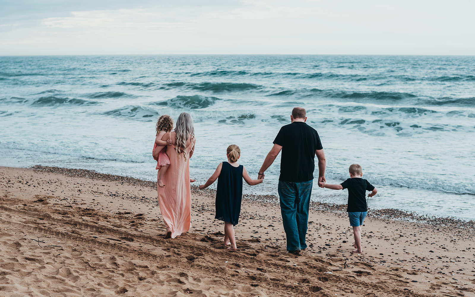 Family holding hands while walking along the water edge at the beach.