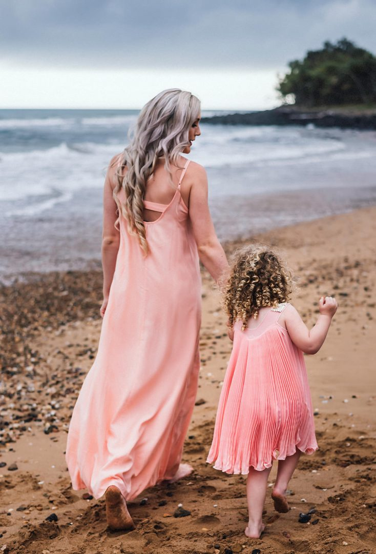 Mother and daughter walking hand in hand at the beach