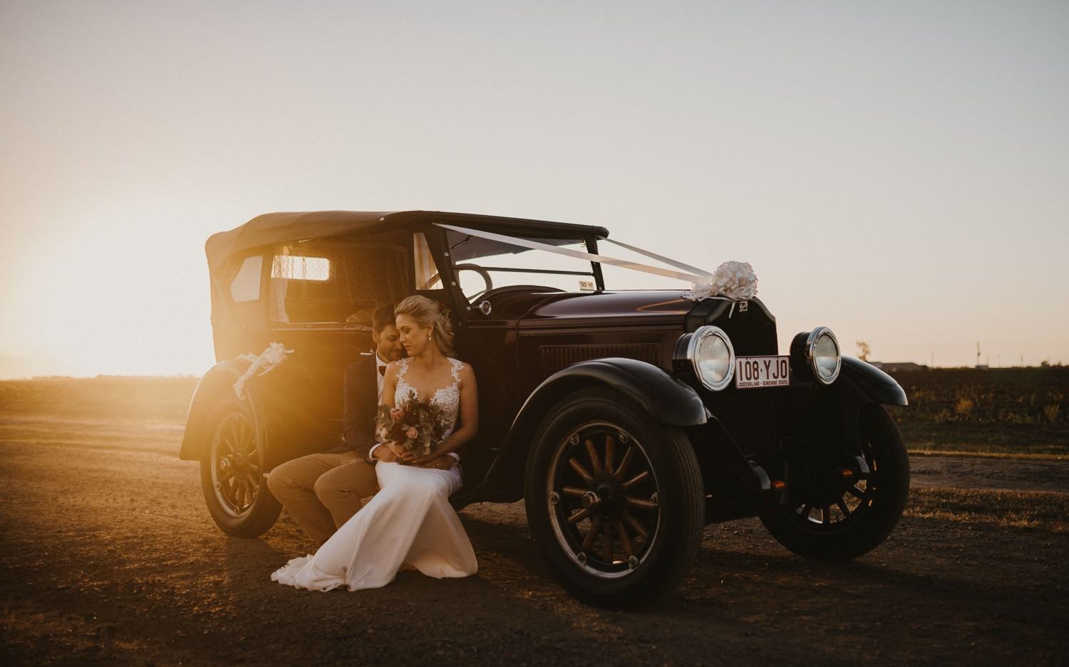 Bride and Groom with vintage car during sunset.