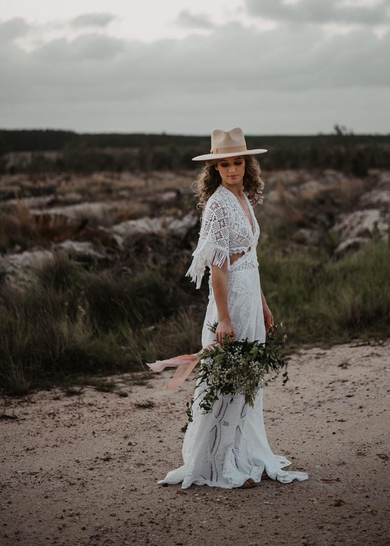 woman in open field wearing a hat and vintage white gown