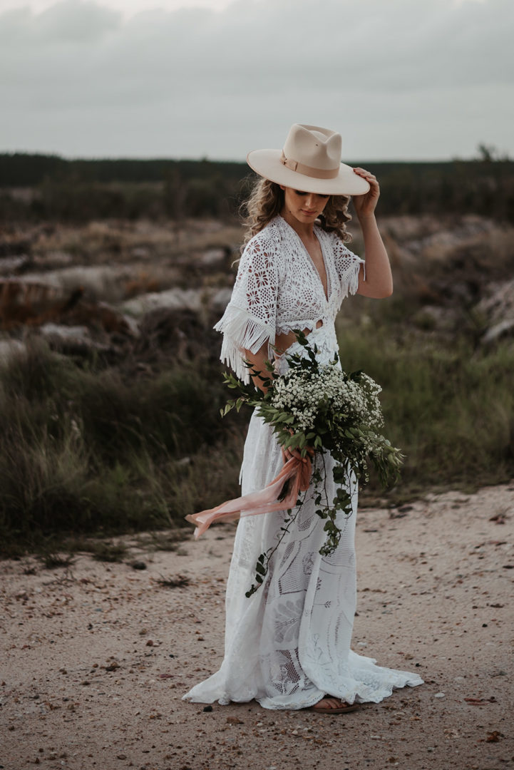 woman wearing hat and carrying a bouquet