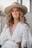 Model wearing a hat and boho white gown