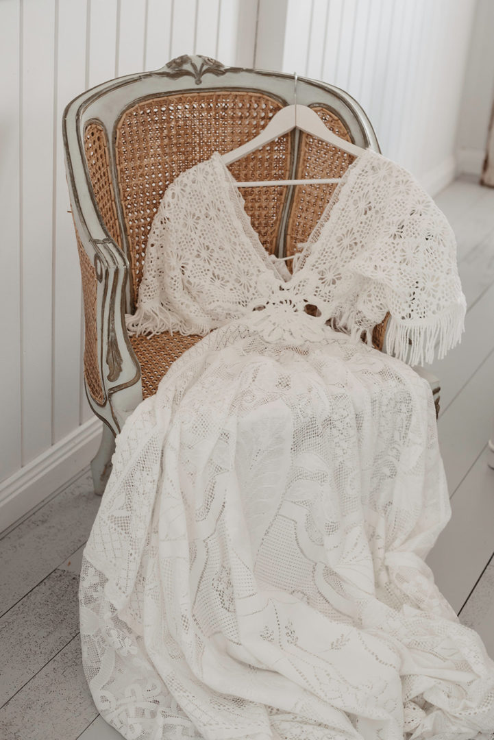 vintage white lace gown laying on a chair