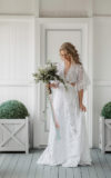 woman wearing vintage gown and holding a bouquet of baby's breath
