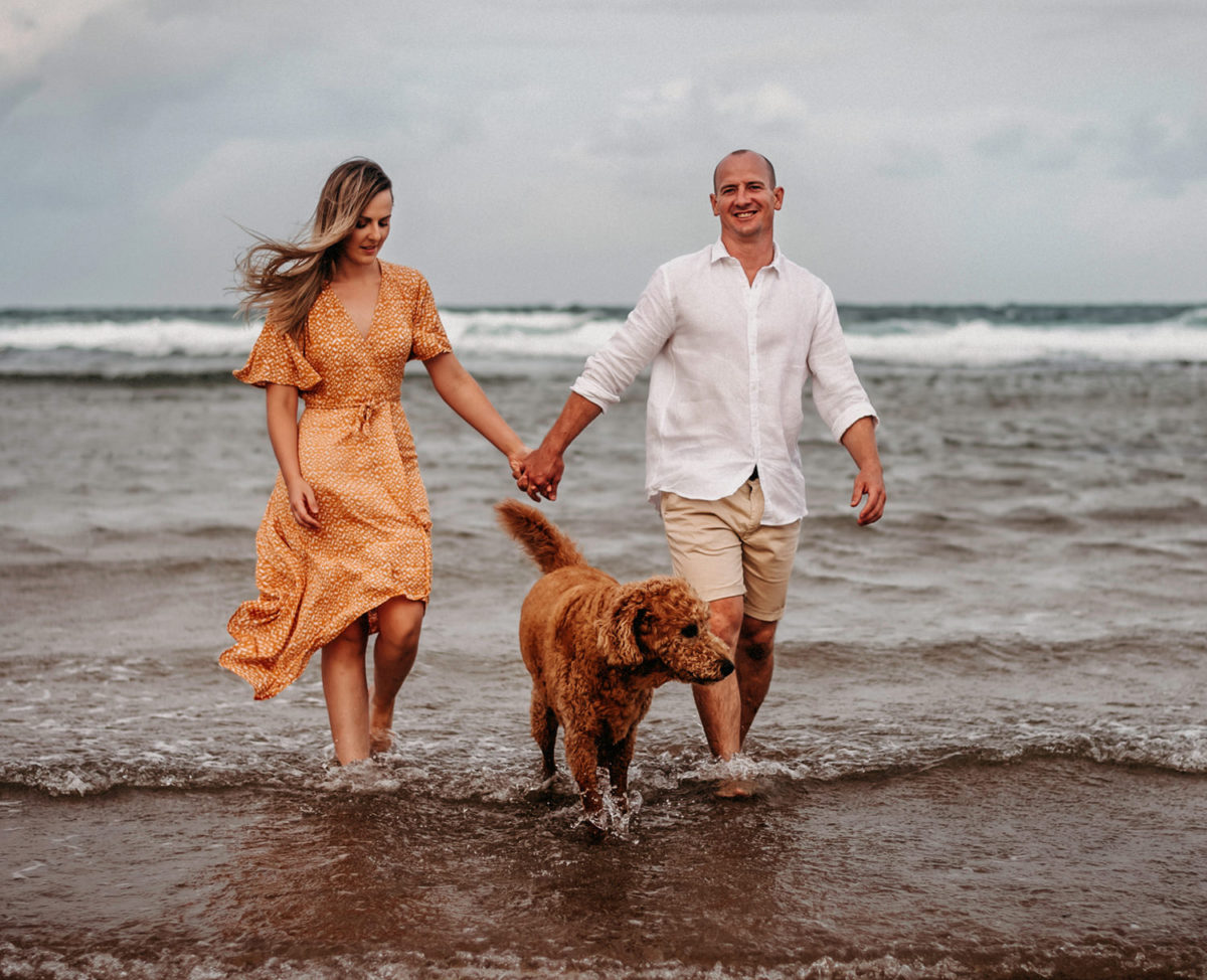 couple walking on the beach with Labradoodle