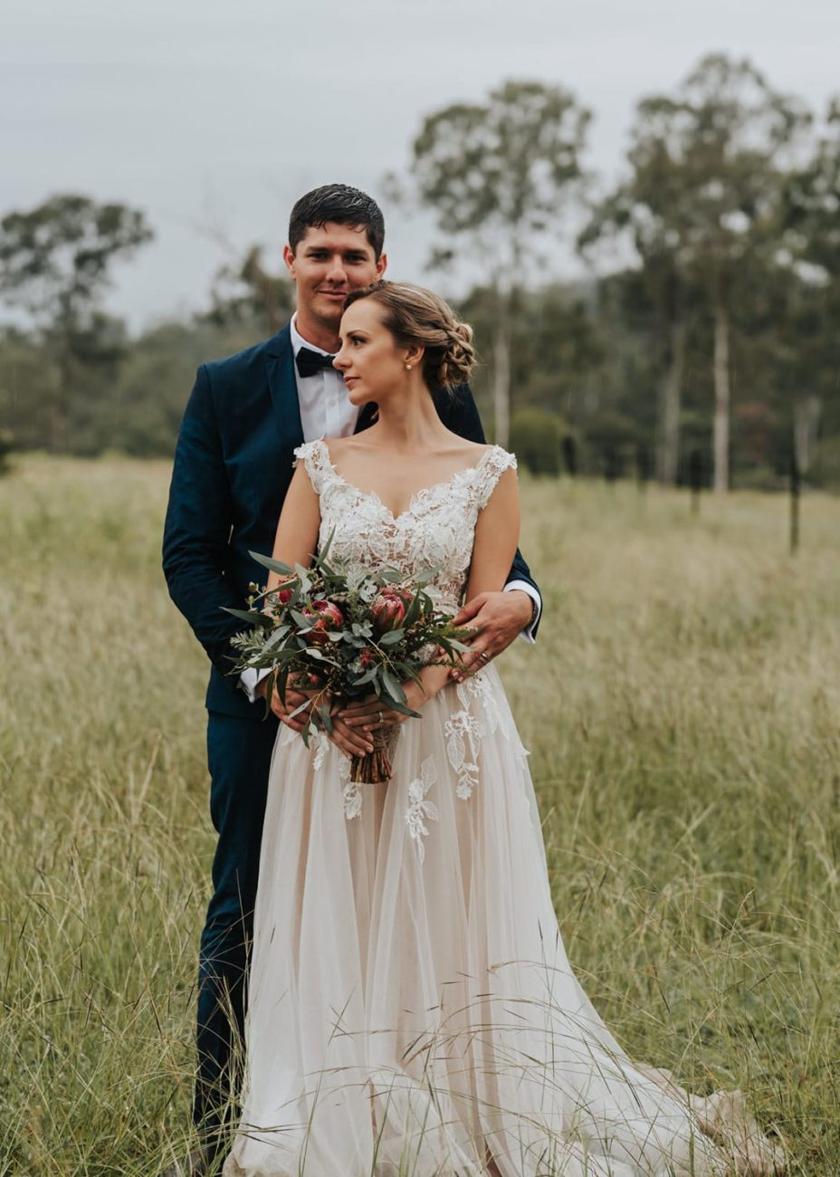 bride standing in front of groom in field